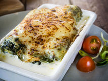 Lasagna in ceramic casserole dish served with tomato and herb Royalty Free Stock Images