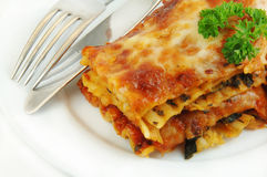 Lasagna Close up with Fork and Knife. Serving of spinach lasagna close up with a knife and fork on a white plate stock photos