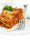 Lasagna with Fork and Knife on White Royalty Free Stock Image
