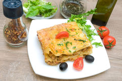 Lasagna with meat, cherry tomatoes, olives and spices on a woode Royalty Free Stock Photos