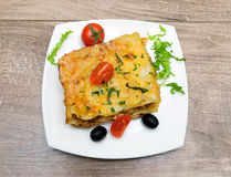 Lasagna with meat, tomatoes, olives and greens on a plate Stock Image