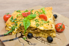 Lasagna with minced meat, tomatoes, olives and greens closeup Royalty Free Stock Photography
