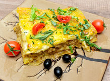 Lasagna, olives and tomatoes on a plate close-up Royalty Free Stock Photos