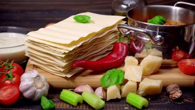 Lasagna pasta sheets, bolognese and bechamel sauce. LRecipe of lasagna - pasta sheets, bolognese and bechamel sauce on wooden table stock footage