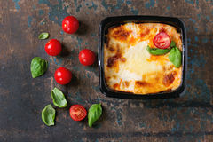 Lasagna in plastic box. Cooked meat lasagna in black plastic box, served with fresh cherry tomatoes and basil leaves over old dark wooden textured background Stock Photography