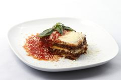Lasagna on plate. Beef lasagna or lasagne topped with grated Parmesan and tomato sauce on white plate. Raw available royalty free stock image