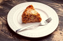 Lasagna on plate. A piece of lasagna on a white plate with a fork Stock Photo
