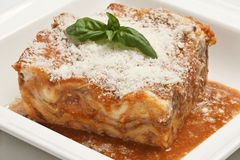 Lasagna portion. With tomato sauce on a white plate Stock Image