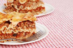 Lasagna on red and white tablecloth Stock Photos