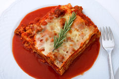 Lasagna with rosemary garnish Stock Photos