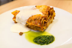 Lasagna with sauce on white plate Stock Photography