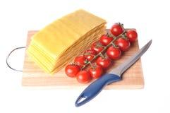 Lasagna sin procesar con el tomate y el cuchillo Fotos de archivo