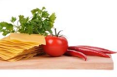 Lasagna, tomate y pimienta sin procesar Imagen de archivo