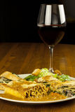 Lasagna and Wine. A plate of organically made lasagna with a caesar salad and a glass of red wine Stock Image