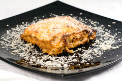 Lasagne. With grated parmezan on black plate Royalty Free Stock Images