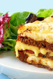 Lasagne. Beef lasagne with melting mozzarella and ricotta cheeses, with a salad Stock Image