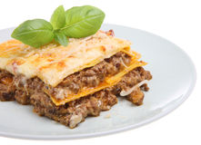 Lasagna or Lasagne al Forno. Freshly baked lasagne made to a traditional recipe and garnished with parmesan shavings and basil leaves Royalty Free Stock Photo