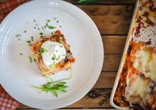 Lasagne al forno casalinghe con panna acida e la erba cipollina fresca su fondo di legno, vista superiore, spazio della copia fotografia stock