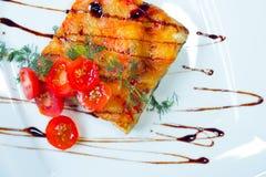 Lasagne al forno con i pomodori su un piatto bianco immagine stock