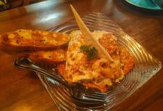 Lasagne al forno del pollo con pane all'aglio fritto su un piatto immagine stock