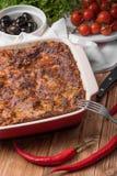 Lasagne al forno fresche in piatto rosso con i pomodori ed i peperoncini rossi delle olive nere sulla Tabella di legno Immagine Stock