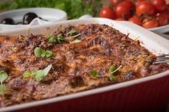 Lasagne al forno fresche in piatto rosso con i pomodori ed i peperoncini rossi delle olive nere sulla Tabella di legno immagine stock libera da diritti