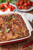 Lasagne al forno fresche in piatto rosso con i pomodori ed i peperoncini rossi delle olive nere sulla Tabella di legno fotografia stock libera da diritti