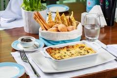 Lasagne al forno fresche in un piatto di cottura con il canestro del pane immagini stock