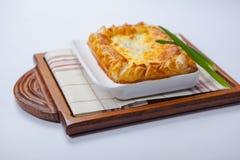 Lasagne al forno nel piatto al forno sul bordo di legno Immagine Stock