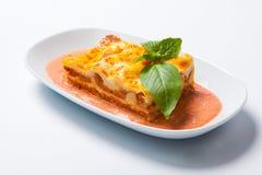 Lasagne al forno su un piatto bianco con l'erba Fotografia Stock
