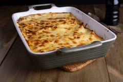 Lasagne al forno in un piatto del servizio con formaggio sulla cima su una vecchia linguetta di legno Fotografia Stock