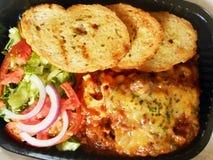 Lasagne mit Brot und Gemüse Stockbild