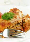Lasagne mit Gabel auf Weiß stockbild