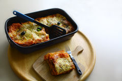 Lasagne with olives. A form with freshly more cooked lasagne, stands in front of it a plate with a portion of this court Royalty Free Stock Photo