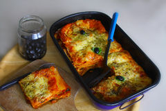 Lasagne with olives. A form with freshly more cooked lasagne, stands in front of it a plate with a portion of this court Royalty Free Stock Photos