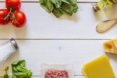 Lasagne, Tomaten, Hackfleisch und andere Bestandteile Wei?er h?lzerner Hintergrund Italienische K?che stockbilder