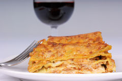 Lasagne verdi al rag�. Macro shot of the typical italian lasagne alla bolognese, with a glass of rd wine in the background. Shallow DOF. Focus is on the Royalty Free Stock Photos