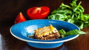 Lasanhas italianas com carne triturada bolonhês, cenouras, e queijo parmesão em uma placa azul cerâmica bonita Copie o espaço, se fotografia de stock