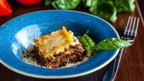 Lasanhas italianas com carne triturada bolonhês, cenouras, e queijo parmesão em uma placa azul cerâmica bonita Copie o espaço, se foto de stock