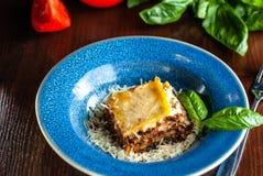 Lasanhas italianas com carne triturada bolonhês, cenouras, e queijo parmesão em uma placa azul cerâmica bonita Copie o espaço, se imagens de stock royalty free