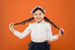 Lasci i vostri capelli parlare per se stesso Bambina sveglia che tiene capelli castana lunghi su fondo arancio Piccolo scolaro fotografia stock libera da diritti