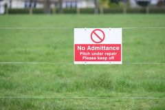 Lasci stare prego il passo dell'erba di sport nell'ambito del segno della riparazione immagini stock