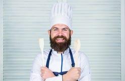 Lascia il gusto di prova Aggiunga alcune spezie Uomo con la barba in cappello del cuoco e tenuta del grembiule che cucinano gli s immagine stock libera da diritti