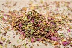 Lascia il tè dell'amaranto, sparso sulla tavola di legno Immagine Stock