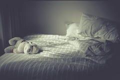 Lasciando la bambola del cane sola da solo sul letto di mattina Immagine Stock