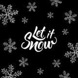 Lasciate nevicare! L'iscrizione ed il natale scritti mano scarabocchiano su fondo nero Fotografie Stock