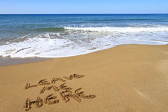 Lascimi qui, scritto sulla spiaggia Fotografia Stock