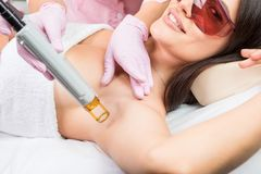 Laser cosmetology Armpit hair removal. Beautiful smiling woman client in red glasses having procedure. Royalty Free Stock Photography