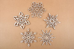 Laser cut wood snowflakes ornaments. Wooden snowflakes on carton surface Stock Photos