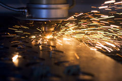 Laser cutting. Metal sheet in factory, with sparks flying around Stock Photography